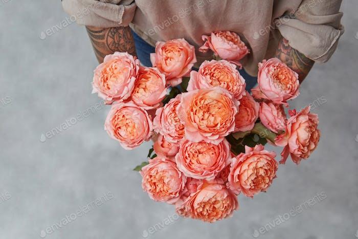Schöner Blumenstrauß von frischen Rosen in den Händen der Frau mit Tatoo in einer Farbe des Jahres 2019 Wohnen