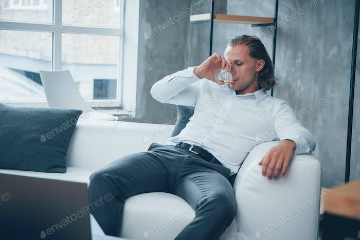 Stress relief. Young man sitting in a front of notebook and drinking whiskey