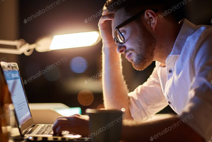 businessman typing on laptop at night office
