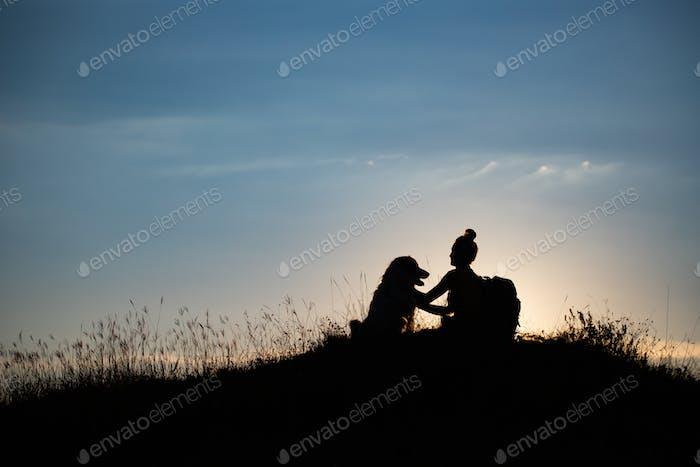Frau mit ihrem Hund sitzt auf dem Hügel im Sonnenuntergang.