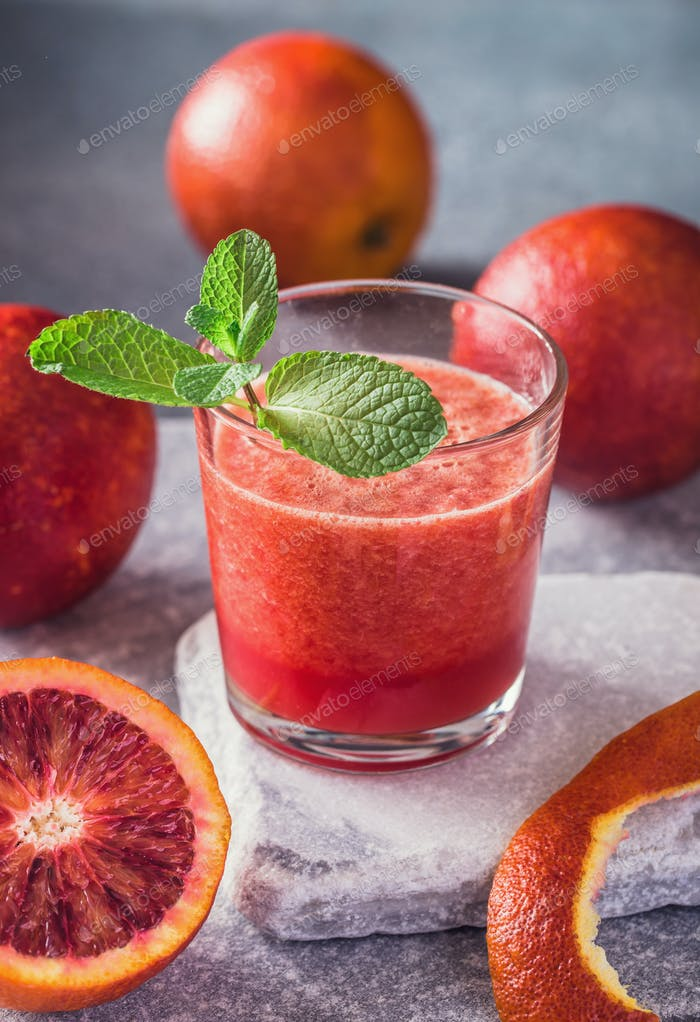 Glass of blood orange fresh on stone background