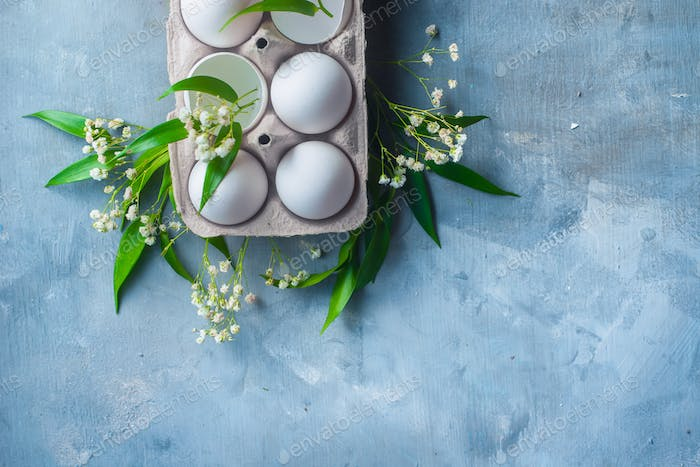 Carton box of fresh chicken eggs on a concrete background with green leaves and spring gypsophila