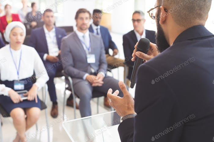 Male speaker speaks with microphone to business people in a business seminar