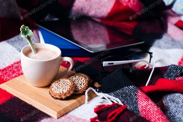 Tablet PC and cup of hot cocoa on a bed