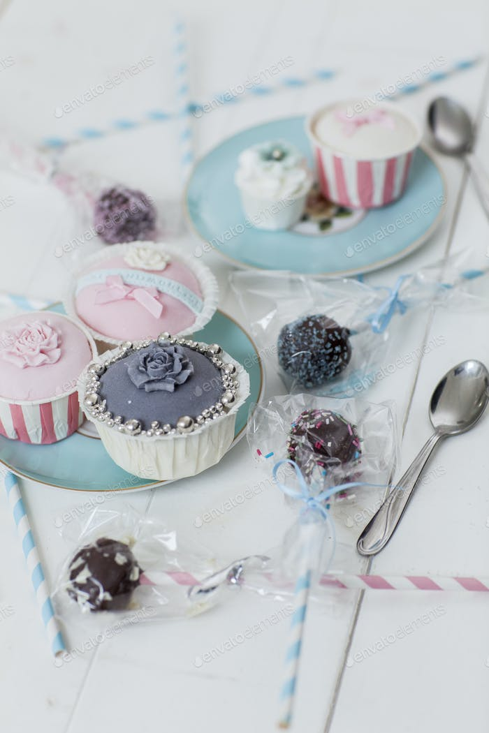 Decorated cupcakes and pops on table