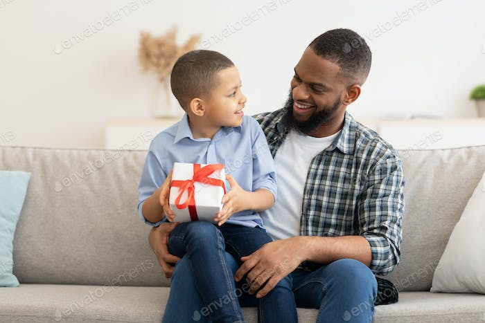 Black Daddy Congratulating Kid Son Giving Birthday Gift At Home