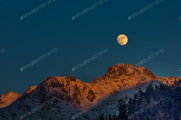 Full moon at sunset on winter mountains