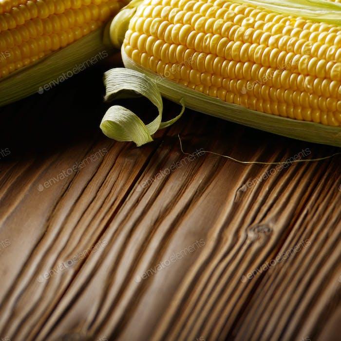 Ripe fresh organic sweet corncobs on wooden table