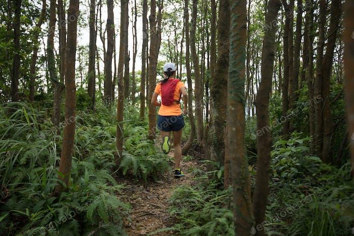 Woman ultramarathon runner running in tropical rainforest