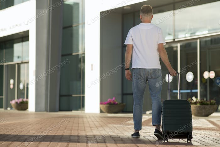 Male tourist walking with baggage at airport terminal