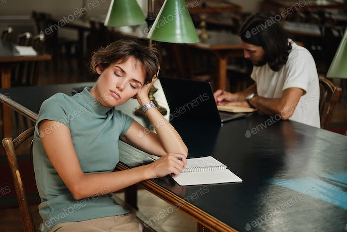 Young tired female student with notepad sleeping during study in library of university