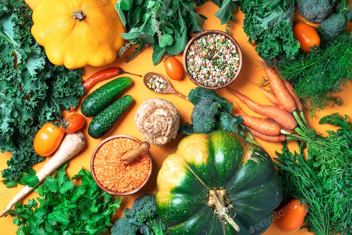 Organic vegetables, lentils, beans, raw ingredients for cooking on trendy yellow background. Healthy