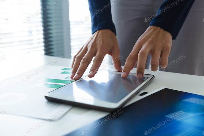 Mid section of female executive using digital tablet at desk