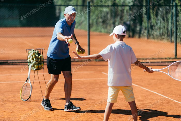 Tennis Instructor with Young Boy on a Clay Court