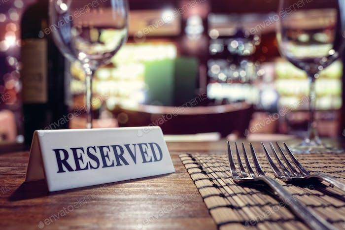 Зарезервированный знак на столе ресторана с фоном бара