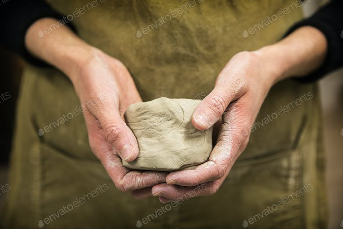Close up of potter holding piece of pottery clay.