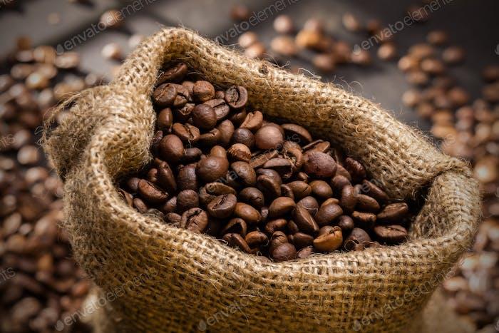 verschüttete Kaffeebohnen in Beutel auf Holz