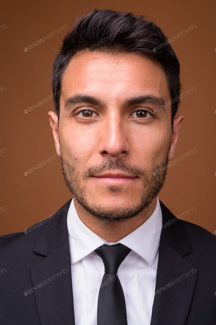 Young handsome Hispanic businessman against brown background