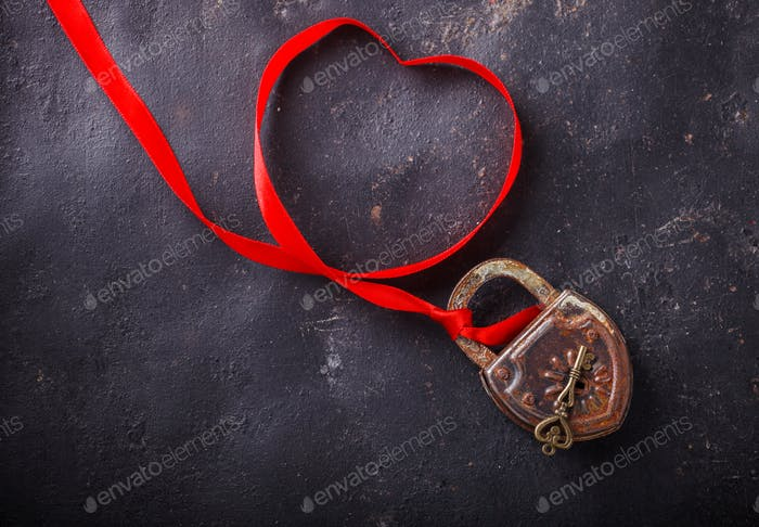 Padlock with key and a red ribbon.Concept Holiday Valentine Day.