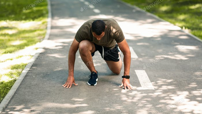 Black sportsman in starting position, ready to run at park on sunny day