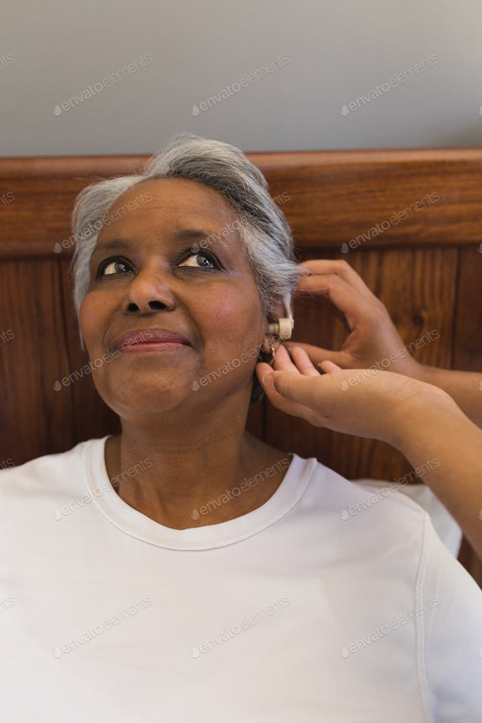 Ärztin passt geduldig ältere Frau mit Hörgerät zu Hause