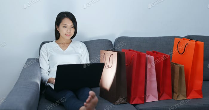 Woman make online shopping on laptop computer at home