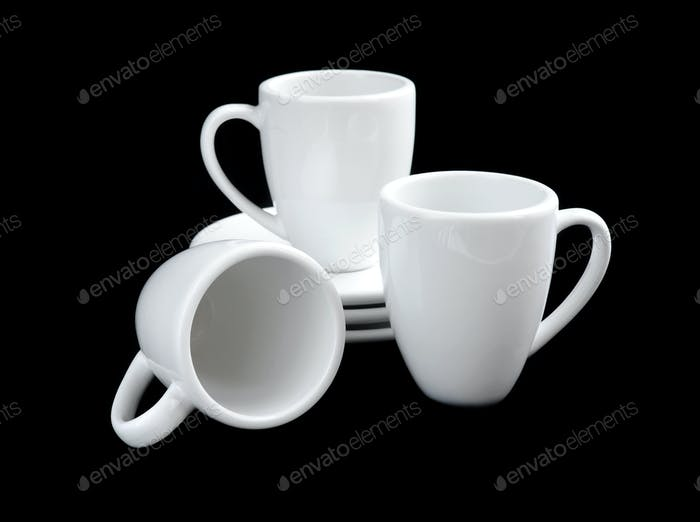 Empty white coffee cups and saucers on black background