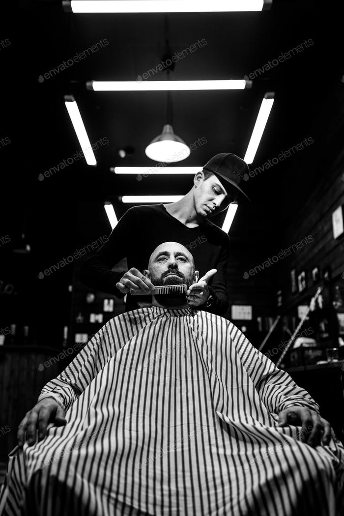 Black and white. The stylish barbershop. The fashion barber tidies up beard of brutal man sitting in