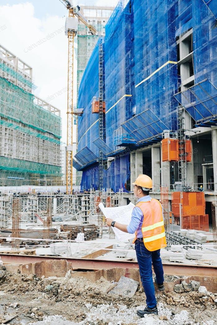 Engineer checking building blueprint
