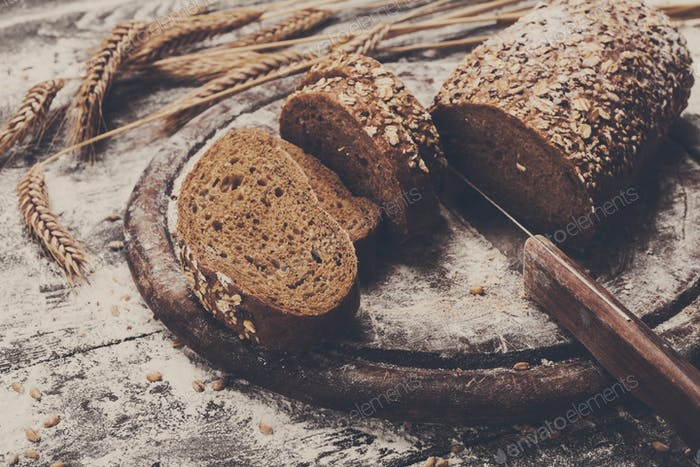 Bakery concept background. Whole grain sliced bread and knife