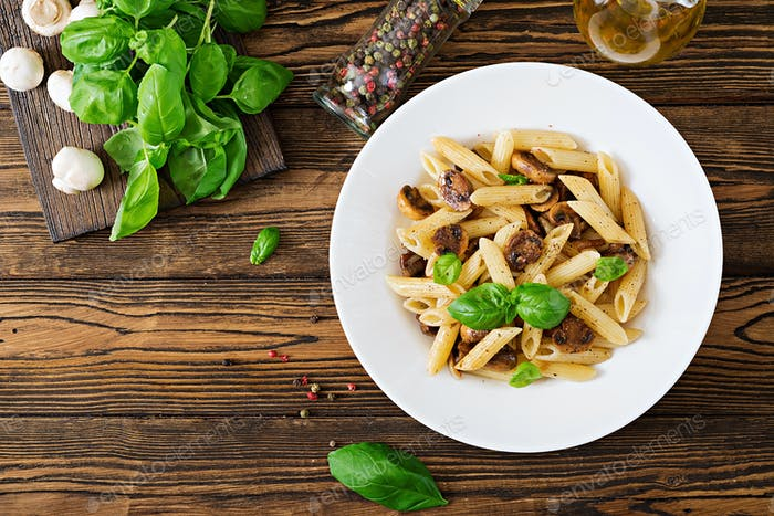 Vegetarian Vegetable pasta penne  with mushrooms  in white bowl on wooden table.