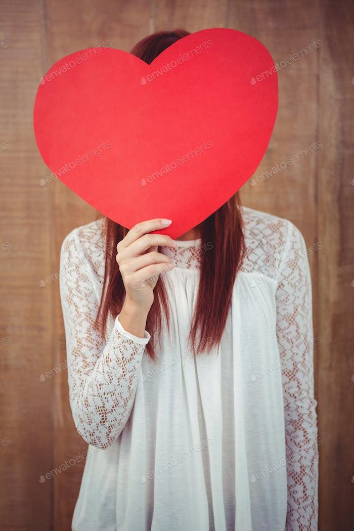 Mujer hipster sonriente detrás de un gran corazón rojo contra Fondo de De madera