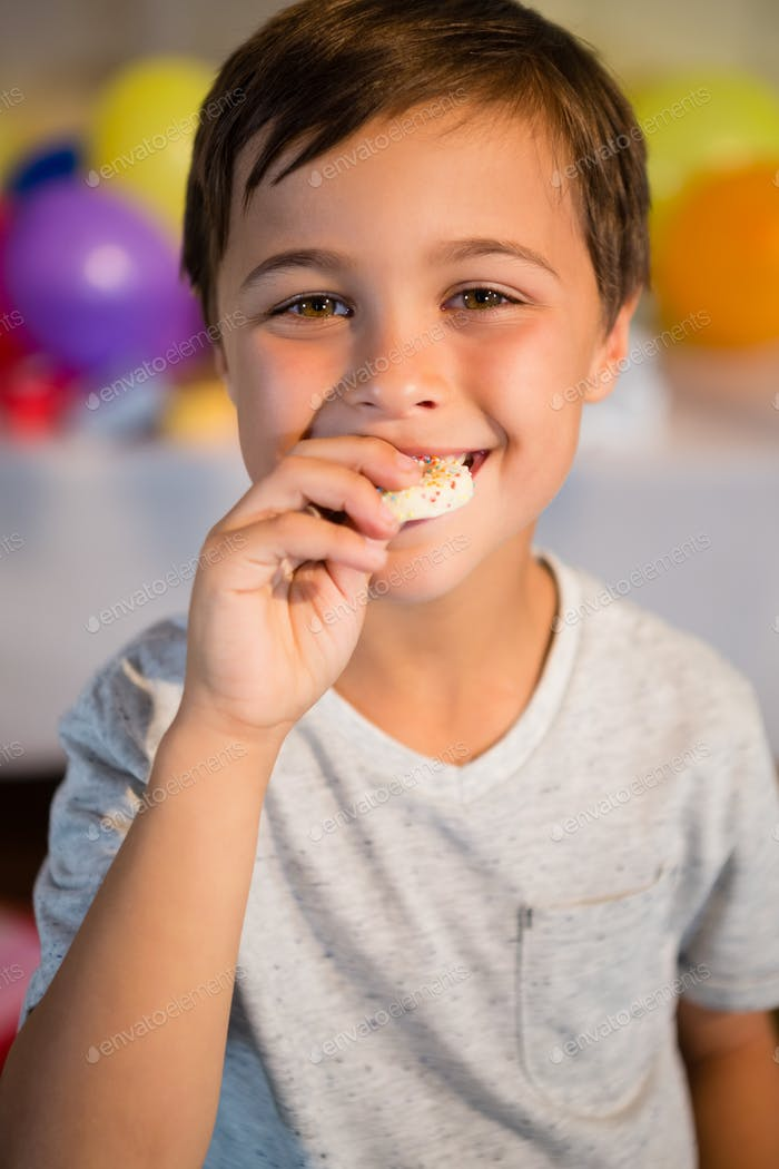 Cute boy eating sweet food during birthday party