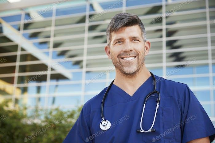 Smiling male healthcare worker outside hospital, portrait