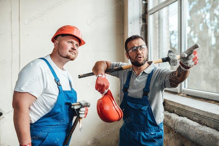 Arbeiter auf einer Baustelle, man zeigt mit einem Finger auf ein Objekt
