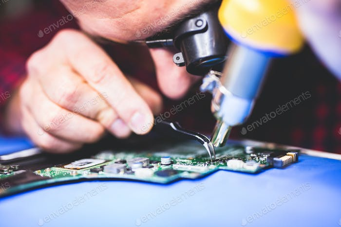 IT worker fixing main board of a computer.