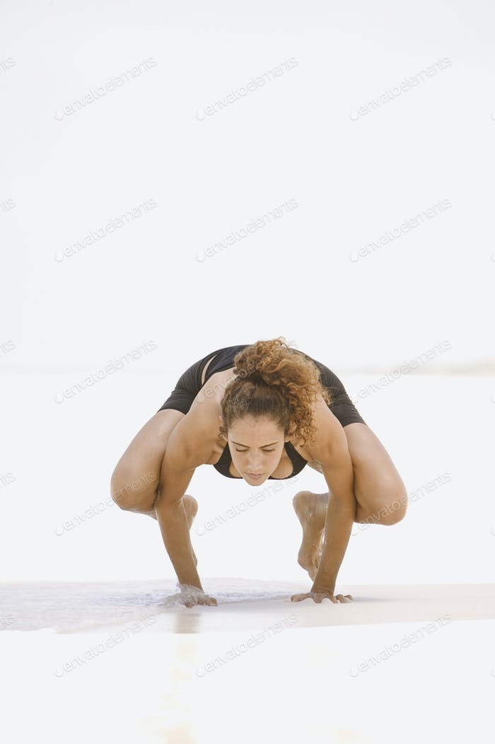 Young woman balancing on her hands