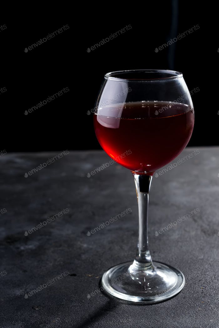 Red wine glass with long shadows on stone table. With copy space for your text