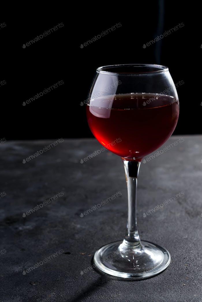 Rotweinglas mit langen Schatten auf Steintisch. Mit Kopierraum für Ihren Text
