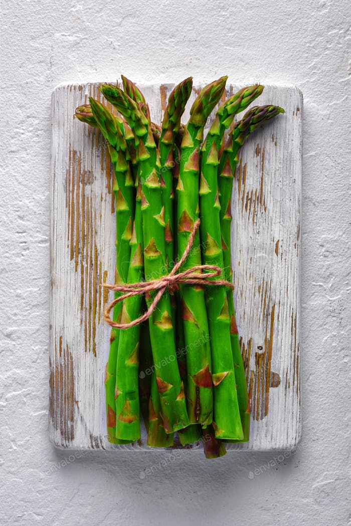 Green asparagus sprout on wooden plate