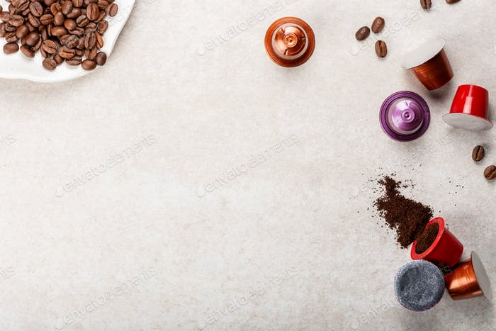 Espresso coffee capsules or pods and coffee beans on grey background