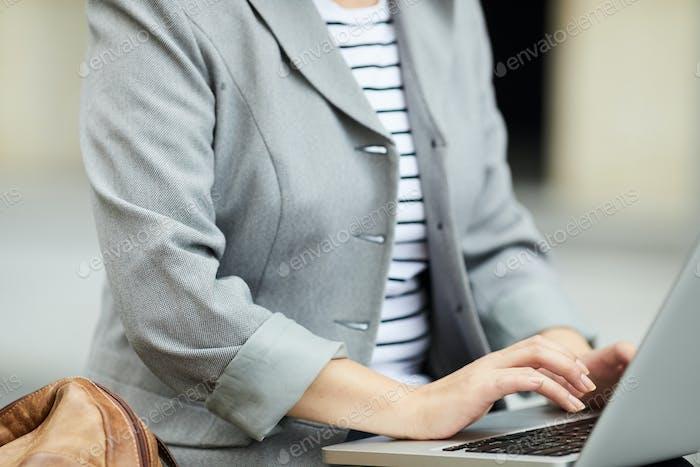 Young Businesswoman using Laptop Outdoors Closeup