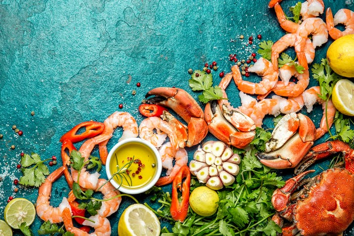 Fresh raw seafood - shrimps and crabs with herbs and spices on turquoise background.