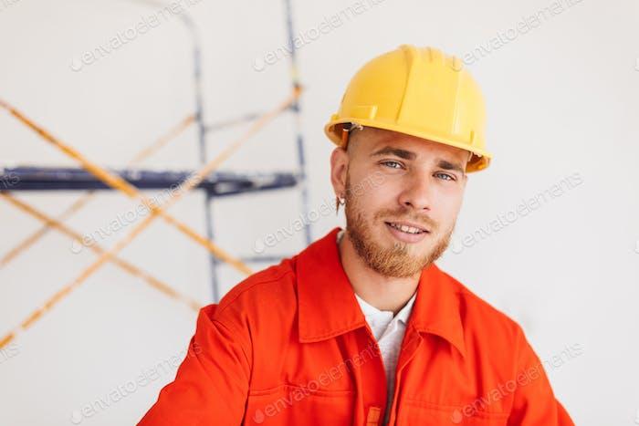 Porträt des jungen Baumeisters in orange Arbeitskleidung und gelb hart