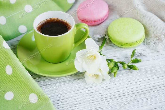Cup of black coffee, white freesia flowers and sweet pastel french macaroons