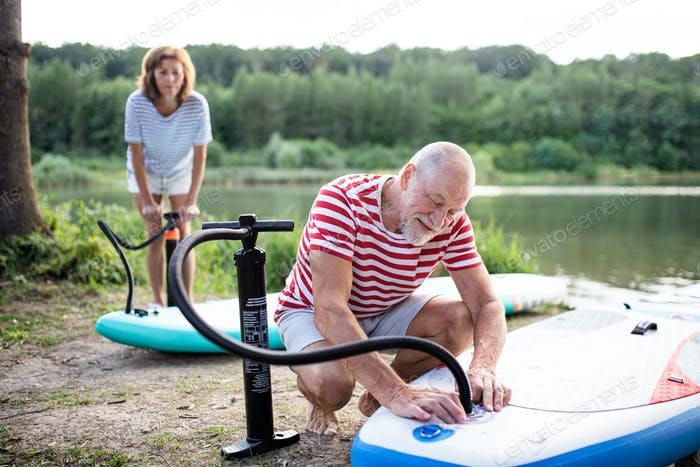 Senior couple getting ready for paddleboarding by lake in summer