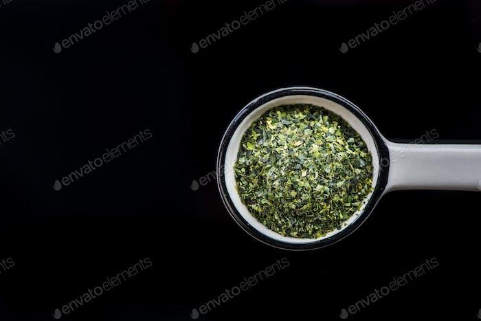 Dried aonori seaweed flakes on spoon