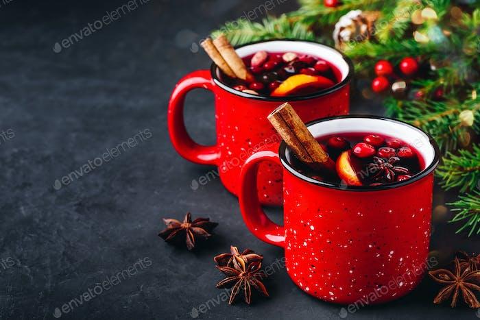 Traditionelles Glühweingetränk mit Preiselbeeren, Orangenscheiben und Gewürzen in roten Tassen