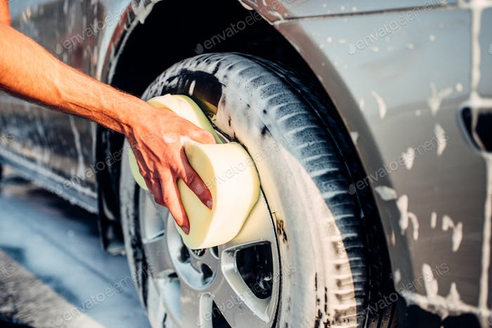 Male hand rubbing car wheel with foam, carwash