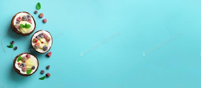Kokos-Eis mit frischen Beeren in Kokosnusshälften auf blauem Hintergrund mit Kopierraum. Ansicht von oben